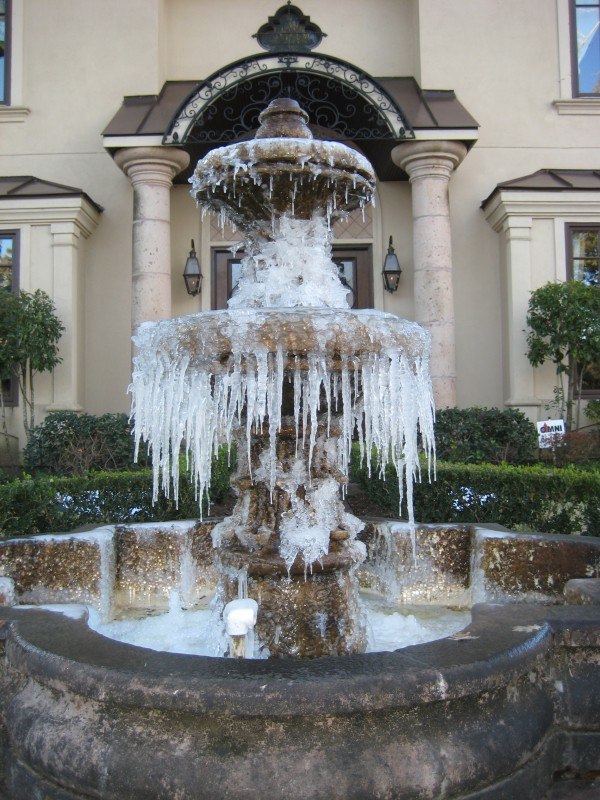 Water fountain frozen in winter in front of Custom Home built by Award Winning Watermark Builders of Bellaire Texas